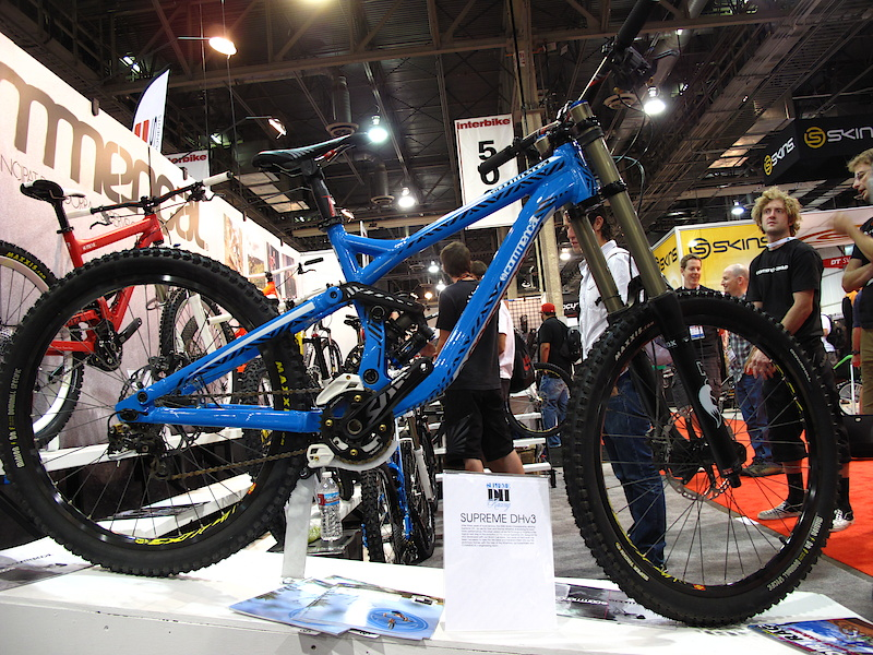 Andorran company Commencal had their latest and greatest Supreme DH on display, which is very different from the previous two versions. There are all sorts of new things going on here, including a lower center of gravity from a shock that sits low in the frame and is actually offset to one side for more drivetrain clearance. If you were to snoop around you'd also find that the blue bike uses press in BB cups, adjustable chainstay length that you tweak with removable chips, and super slick cable routing from front to back. The all important head angle sits at 64 degrees, but by spec'ing a 1.5