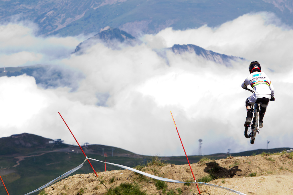 Danny Hart flying over the clouds in the upper part of the giant air downhill